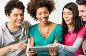 Group of happy friends laughing together with digital tablet