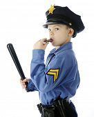 A young elementary boy looking back at the viewer as he wields his billy club and blows his whistle.  On a white background.