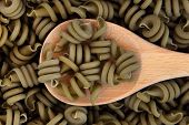 Spinach trot olle pasta on a wooden spoon and forming a background.
