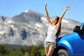 Summer car travel freedom woman in Yosemite National Park with arms raised up cheerful and happy. Summer road trip traveler concept from Yosemite National Park, California, USA.