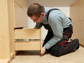 Carpenter installing wardrobe drawers in walk-in closet