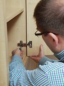 Carpenter fitting wardrobe hinge doors in walk-in closet