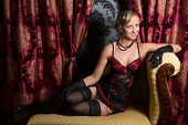 Sexy retro woman in twenties style on an antique chaise longue