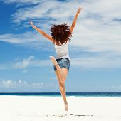 happy young woman jumping on the beach