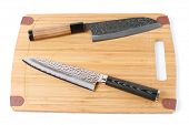 Two top grade japanese knives on bamboo cutting board, isolated