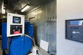 Large industrial diesel generator for backup power with control panel.