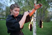 A girl in a black dress shows a fire show with chain.