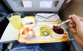 Breakfast in plane (fruit, small bun, juice and tea). Passenger tries tea by teaspoon.