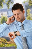 Businessman on phone call checking time on watch, looking worried, standing outside of office.