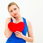 young lonely sad woman holding red valentine heart