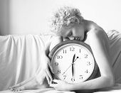 Conceptual portrait of woman in bed with big clock, black and white photo.
