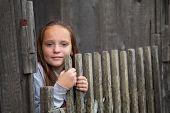 Teengirl standing near vintage rural fence