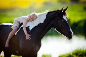 stock photo of petting  - Child sits on a horse in meadow near small river - JPG