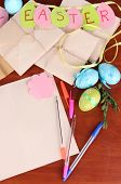 Writing letter of congratulations to Easter holidays on wooden table close-up