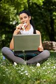 Young woman sitting in grass in park, using laptop, eating club sandwitch.
