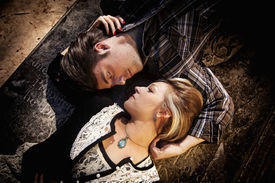stock photo of morbid  - couple looking at each other while laying in opposite directions - JPG