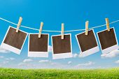 stock photo of polaroid  - Old polaroid film blanks hanging on a rope held by clothespins - JPG
