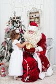 Saint Nicolas gives Christmas gifts to the little girl