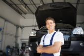 picture of car repair shop  - portrait of female client with arms folded in auto repair shop - JPG