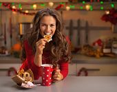 Happy Young Woman Having Eating Christmas Cookies In Kitchen