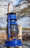 Blue Vintage Kerosene Lamp Hangs On Old Outdoor Fence