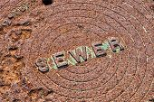 picture of manhole  - Rusty Metal Urban Manhole Sewer Cover With Lettering - JPG