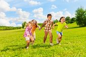 stock photo of 7-year-old  - Group of little 6 and 7 years old kids boys and girls running holding hands together in the park - JPG