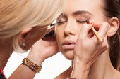 Beauty stylist applying eye make-up to the eyelids of a young model as she prepares for a photo shoot or special occasion