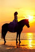 Beautiful woman riding a horse at sunset on the beach. Young beauty girl with a horse in the rays of the sun by the sea.