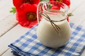 Milk In Pitcher  On Wooden Table
