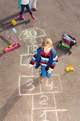 stock photo of hopscotch  - Boy jumping on the hopscotch game drawn on the asphalt looking up - JPG