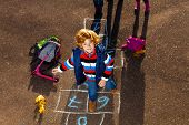 foto of hopscotch  - Nice blond boy jumping over hopscotch game after school with bags and scooter laying near - JPG
