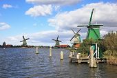 The village - an ethnographic museum in Holland. Four windmills and berthing columns on the bank of