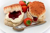 stock photo of devonshire  - Traditional Afternoon Tea of Devonshire scones topped with clotted cream and strawberry jam often served with coffee or tea