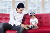 Young Father Reading Story Book With His Baby