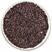 black rice heap in glass bowl  top view surface close up isolated on white background