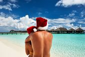 Couple in santa's hat on a tropical beach at Maldives
