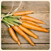 Bunch of carrots over old wood background. Filtered to look like an aged instant photo.