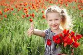 Happy little girl on poppy meadow giving thumb up