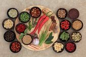 Large herb and spice selection on a wooden board, in bowls and loose.