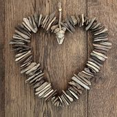 stock photo of driftwood  - Driftwood love heart with small wooden pieces over old oak background - JPG