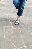 foto of hopscotch  - girl hops in hopscotch outdoors in sunny day