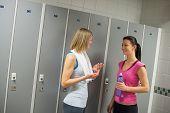 Happy fit women talking in locker room at gym