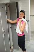 Smiling woman standing by open locker in changing room at gym
