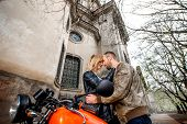 Couple Embracing Near The Motorcycle On The Old City Background