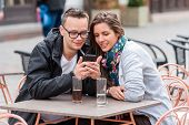 Couple looking on smartphone while sitting at coffee shop table