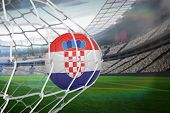 Football in croatia colours at back of net against large football stadium with lights