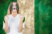 Excited nigeria fan in face paint cheering against nigeria flag in grunge effect