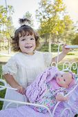 Adorable Young Baby Girl Playing with Her Baby Doll and Carriage Outdoors.