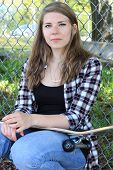 Teenage girl with skateboard leaning against a chain link fence.